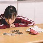 お金を見つめる女の子